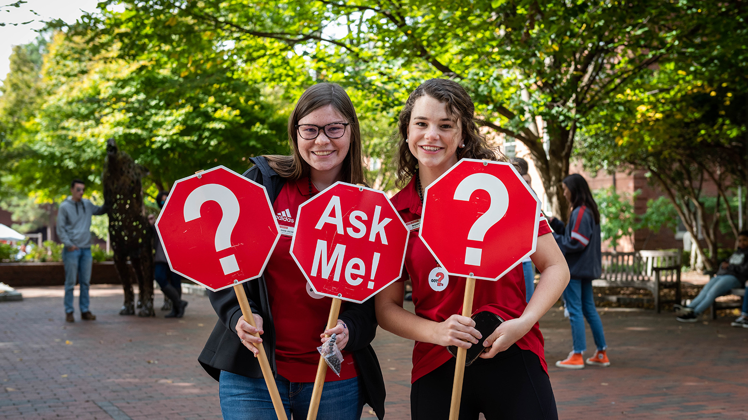Students holding Ask Me sign in front of copper wolves on NCState Campus