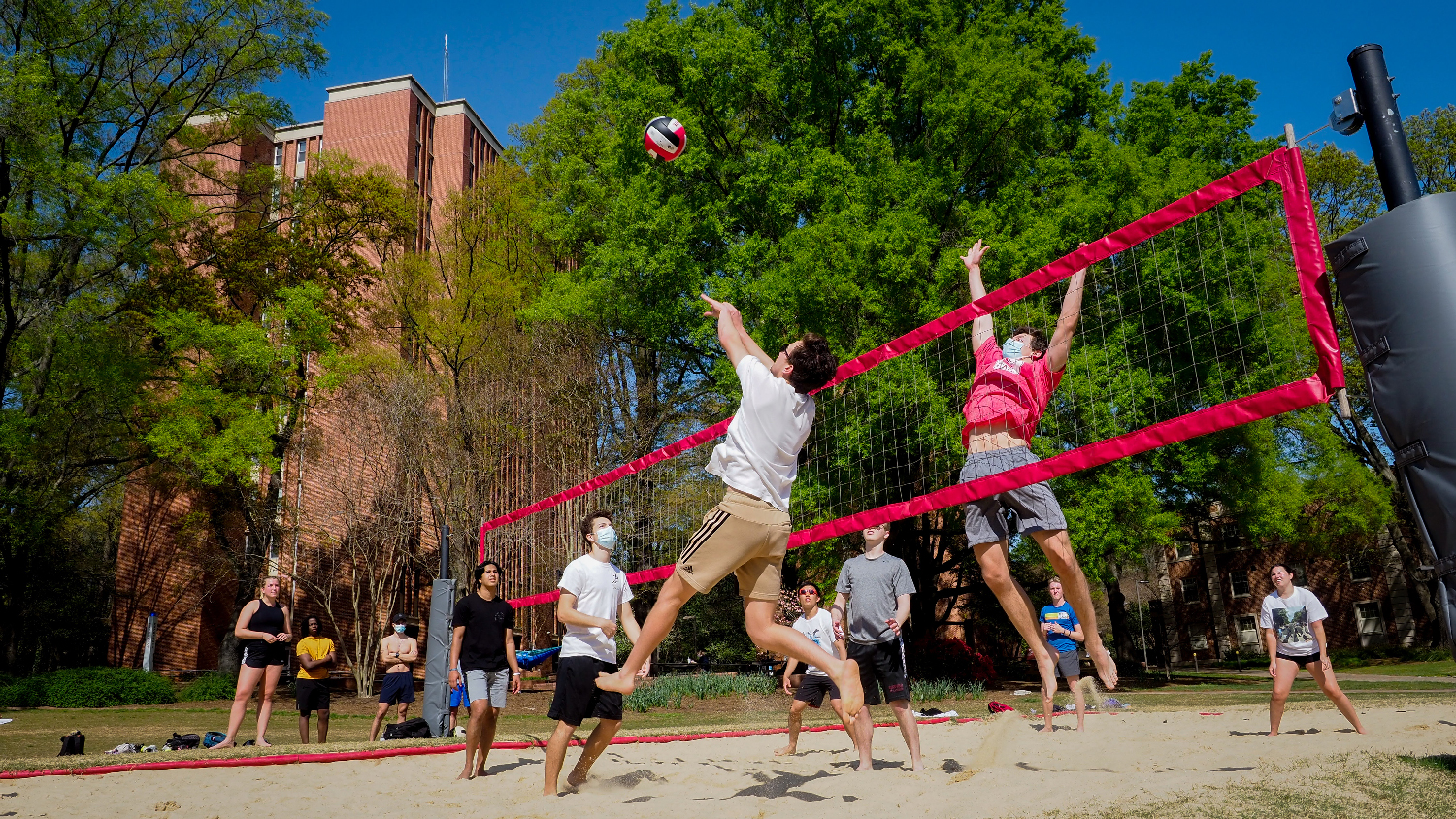 Students enjoy a spring afternoon at Tucker Beach playing volleyball.
