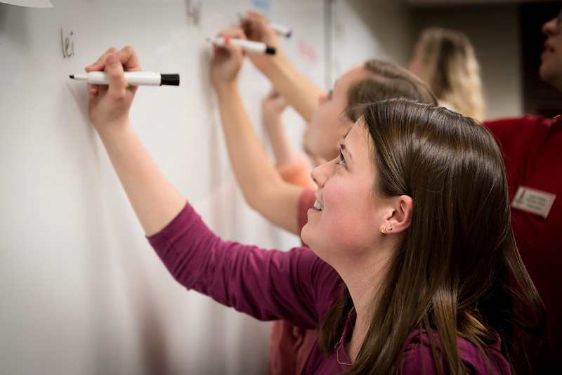 Student writes on whiteboard