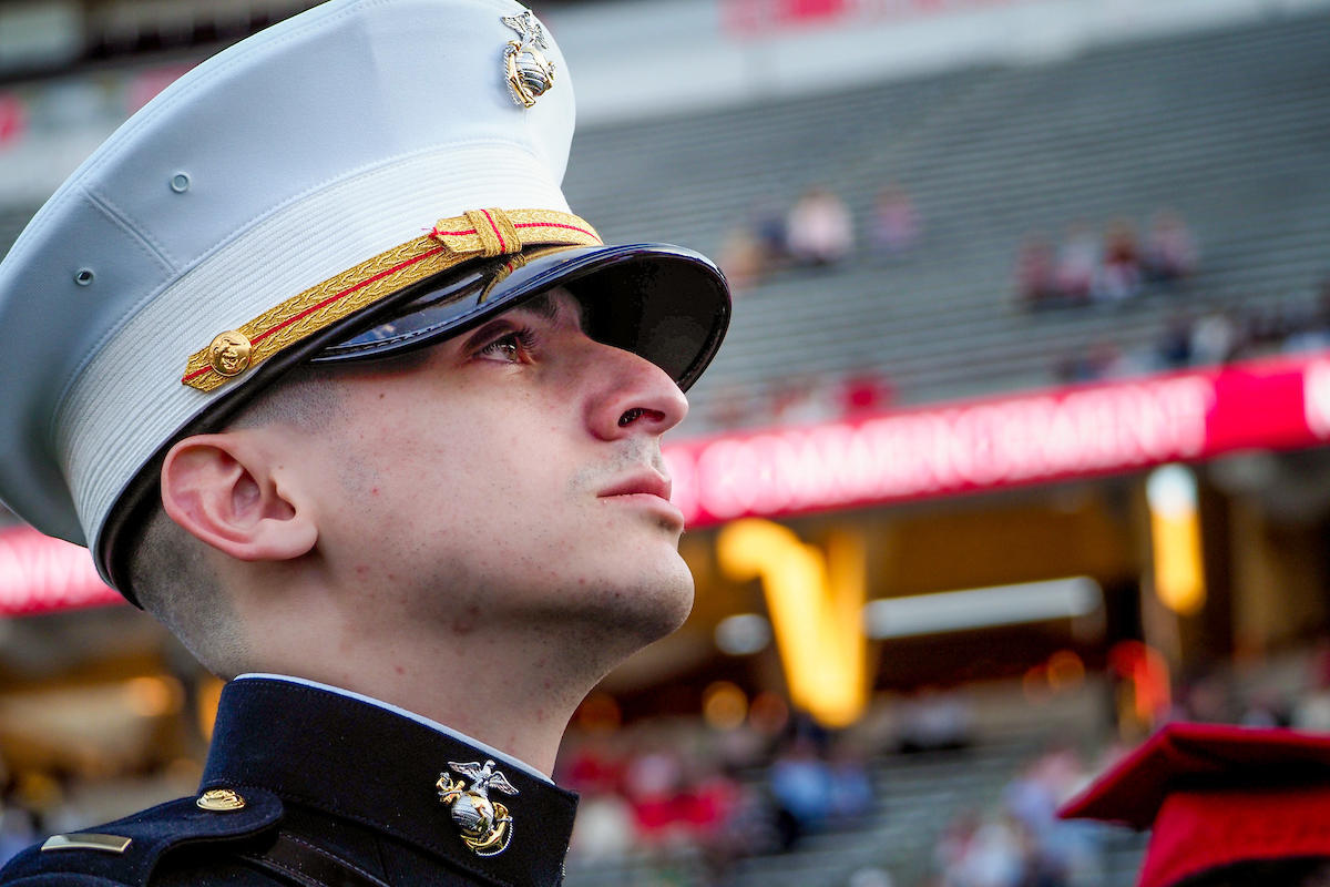 A newly commissioned officer/NCState graduate listens to Russell Wilson's presentation during the spring 2021 graduation ceremonies.