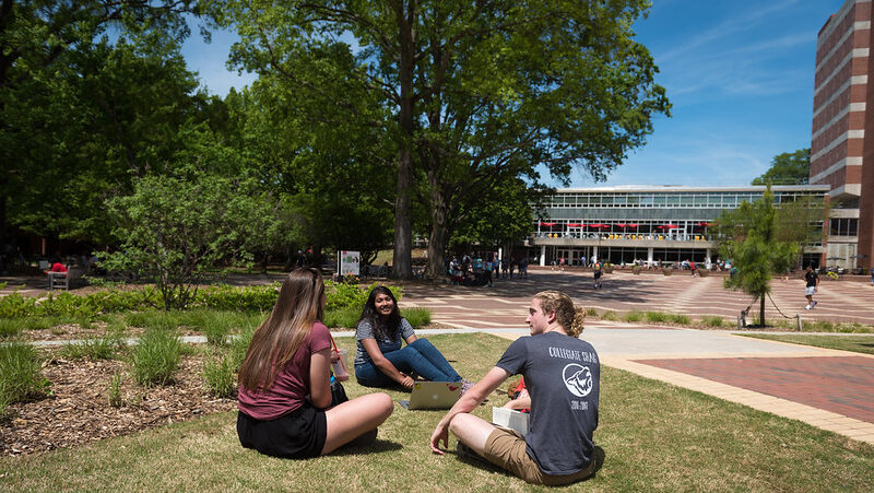 Students sit outside in the Brickyard