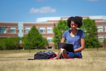 student on laptop in grass